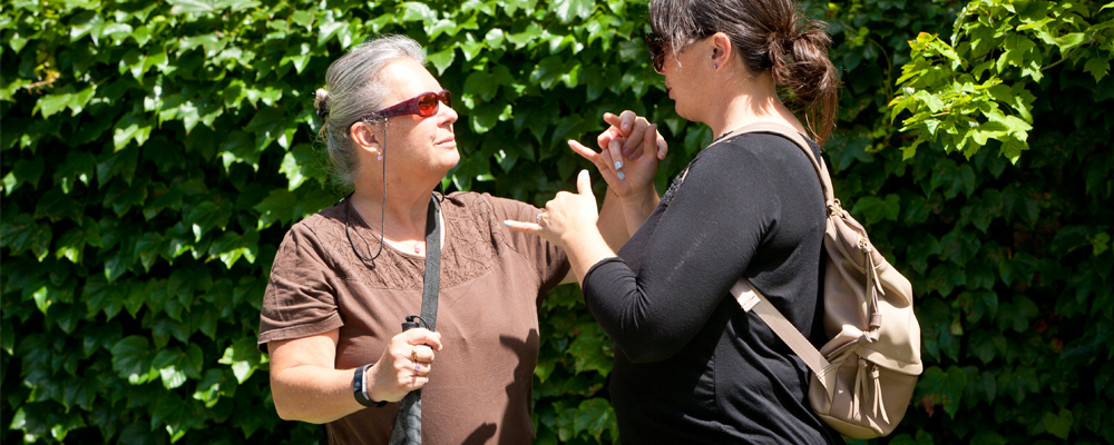 Two woman engage in two hand manual communication outside